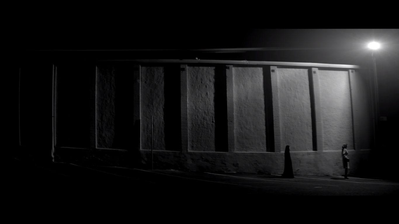 Wide shot of two figures walking on a dark sidewalk. One is cloaked all in black.