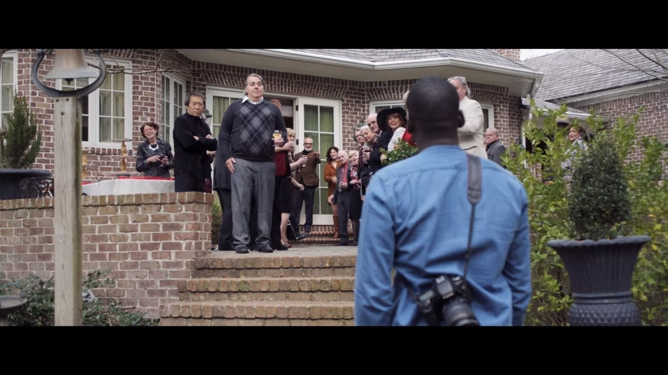 a group of white people people greet a black man in Get Out