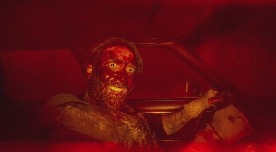 Nicolas Cage covered in blood and grinning inanely while driving a car in Mandy