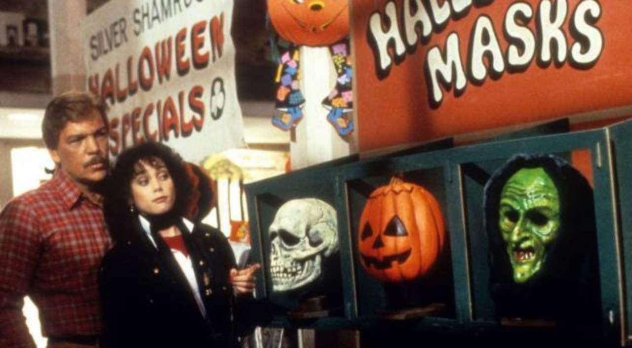 A man and woman observing Halloween masks in a store
