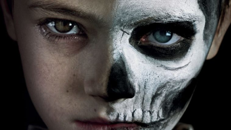 a boy with half his face painted like a skeleton