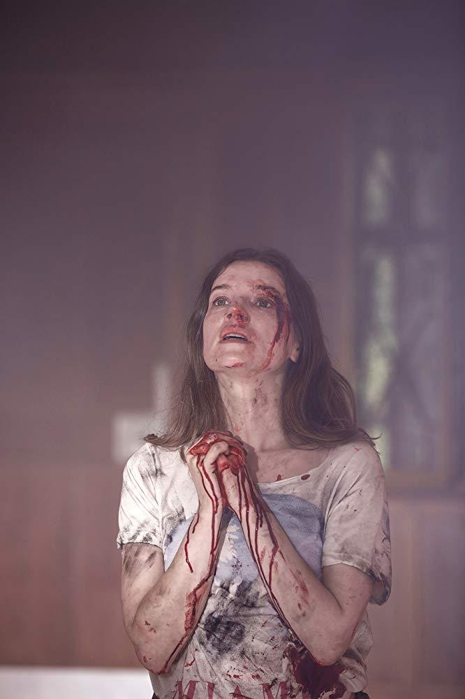A woman kneels in prayer in A Dark Song