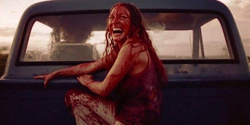 Sally (Marilyn Burns) barely escapes Leatherface as she speeds away laughing maniacally.