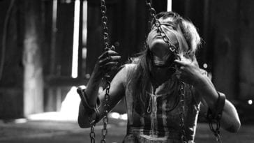 A young woman sits on a swing with a blindfold on