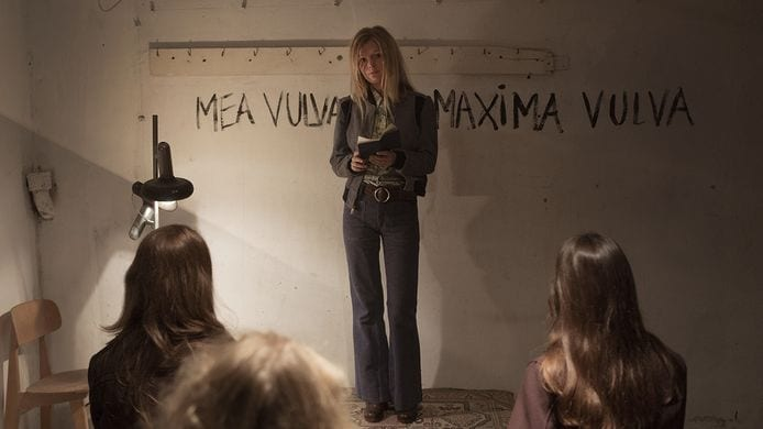 women gather in room with words written in red on wall: mea vulva mea maxima vulva