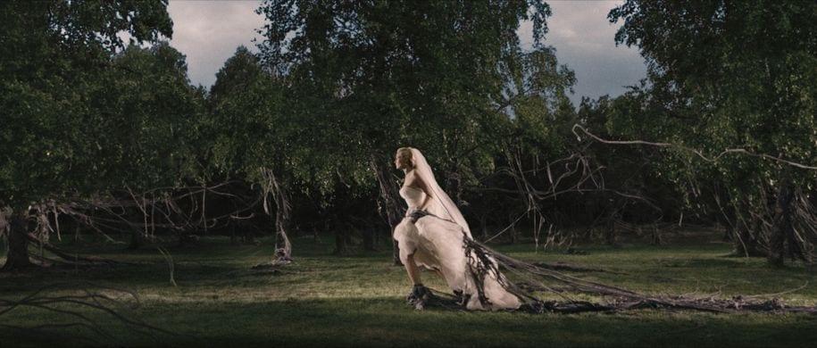 Bride from Melancholia walking through black gunk in stylized shot