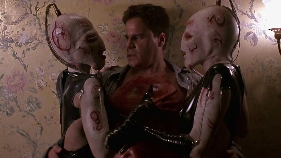 Detective Joseph Thorne (Craig Sheffer) is seductively caressed in an uncomfortable way by two female Cenobites in Hellraiser: Inferno.