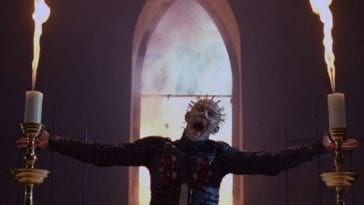 Pinhead stands in front of a church window.