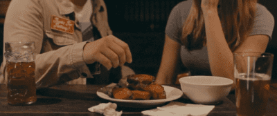 The chests of a male and female at a dinner table, the man reaches to pick up a chicken wing