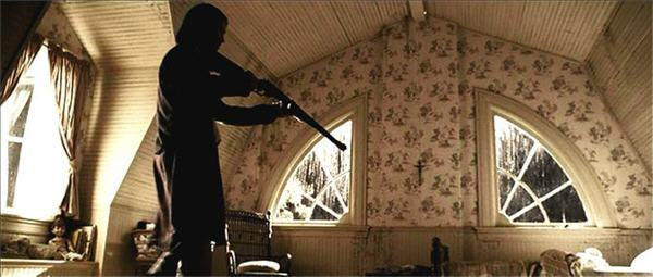 Man Ronald DeFeo Jr. holds up a shotgun in his house's attic as he prepares to kill his next family member in The Amityville Horror (2005).