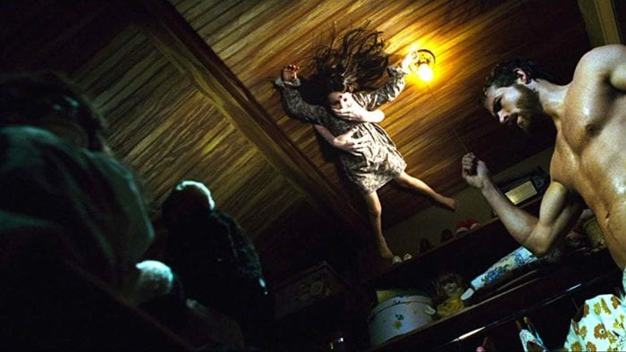 The ghost of young girl Jodie is held against ceiling while man George Lutz stands below not seeing her in The Amityville Horror (2005).