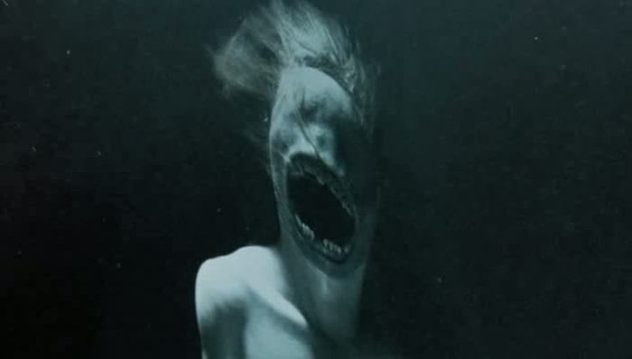 A female ghost with an eyeless face and enlarged mouth screams inside a dunk tank.