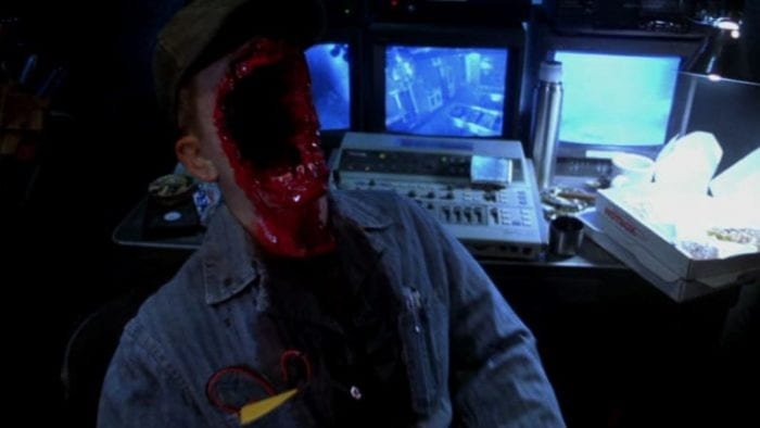 A man sits in a chair in front of some security cameras, his face bloodily hollowed out.