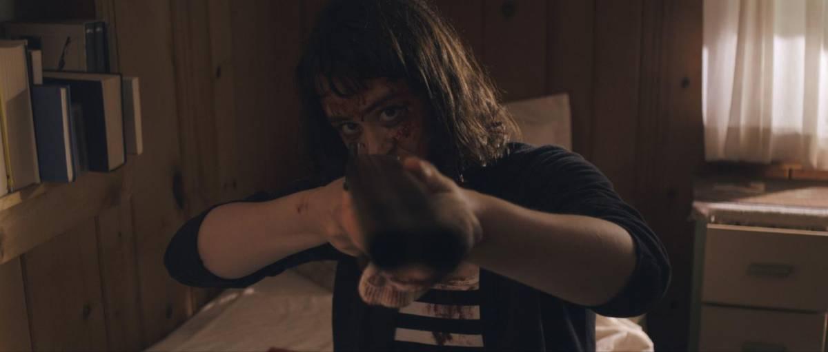 Hoffman as Amanda pointing a shotgun at the camera in Get My Gun