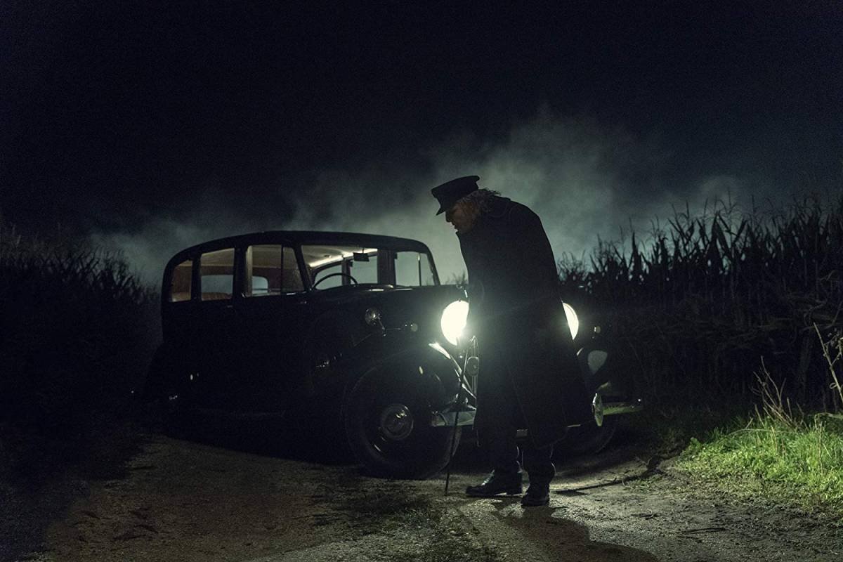 Zachary Quinto in the AMC TV adaptation of NOS4A2 as an old man with a stick standing in front of a 1930s car with its headlights on at night on a dirt road