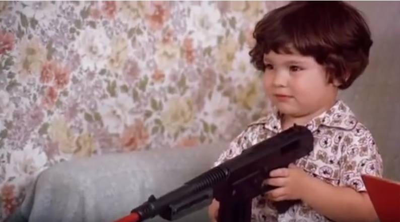 A toddler holds a toy automatic rifle