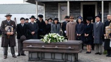 The Nakayama and Furuya families stand around the coffin of Mrs Furuya at her funeral