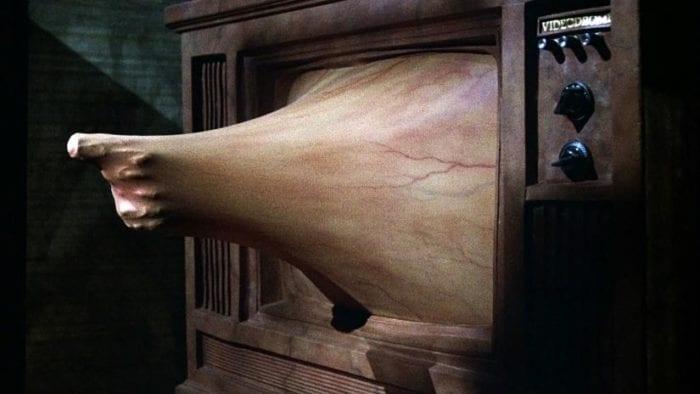 Gun protruding from television through fleshy, veiny membrane