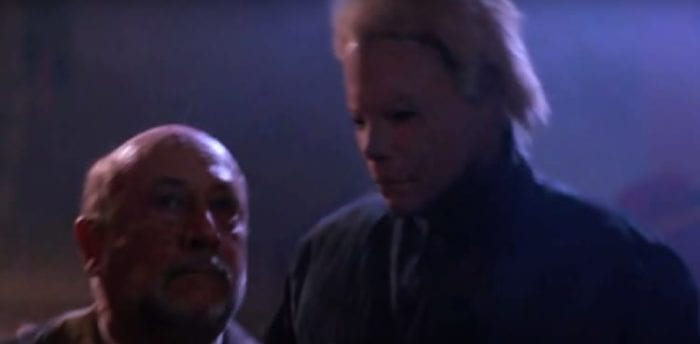 Micheal, in a blond mask, sneaks up on Dr Loomis.
