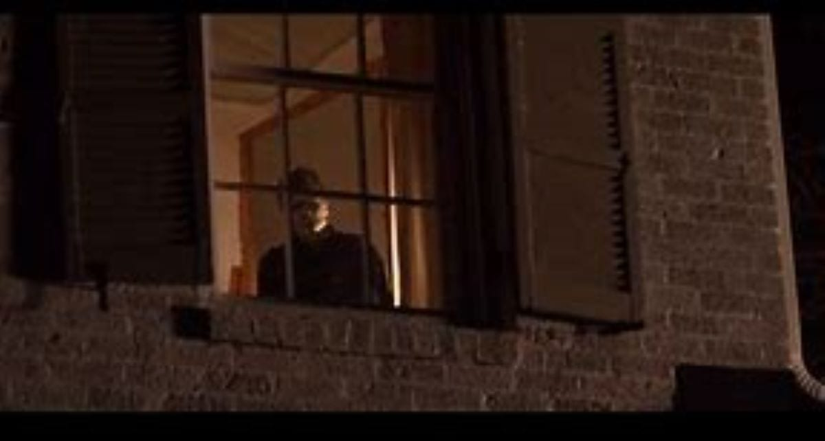 The killer Michael Myers stands in a bedroom window in Halloween