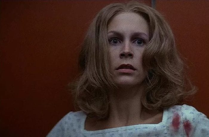 Laurie Strode (Jamie Lee Curtis) is a hospital gown in an elevator as Michael approaches.