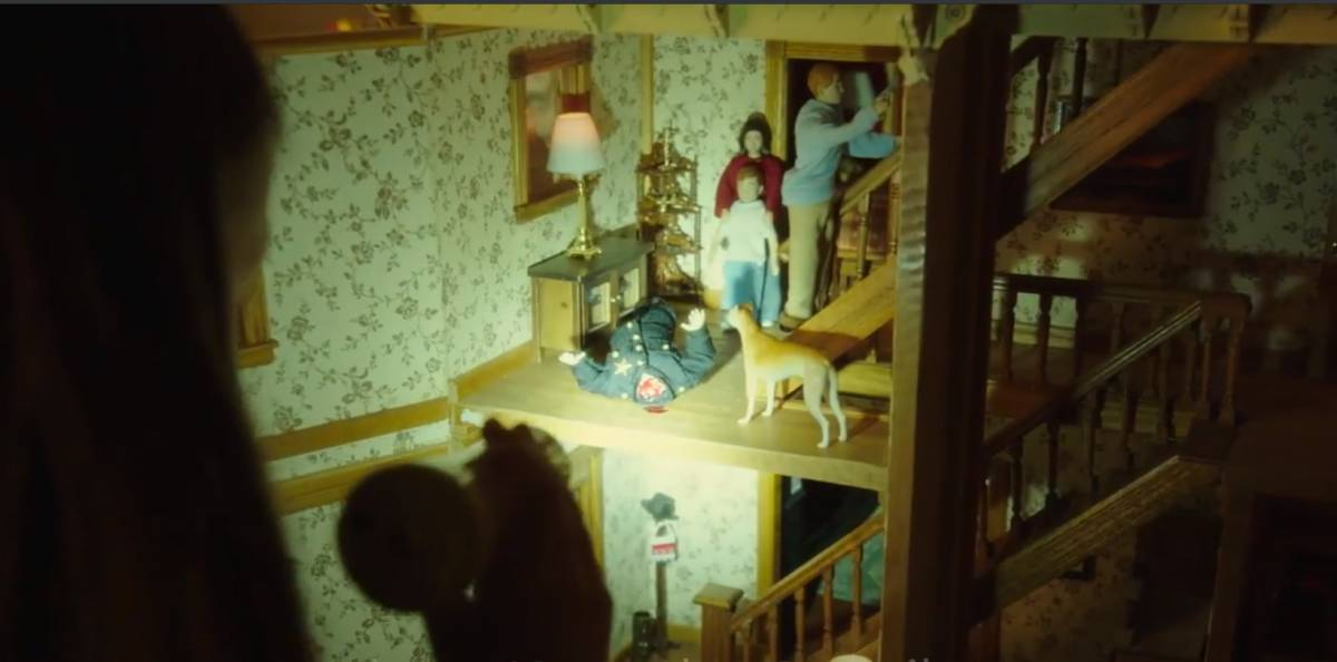Evie shines a flashlight on her dollhouse as the doll family stands around a police officer doll with his head severed.