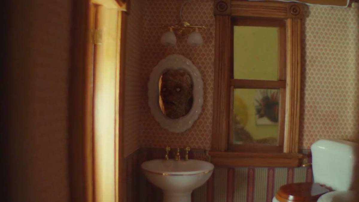 """Image of the severed corpse doll head in the dollhouse bathroom mirror in Creepshow's """"The House of the Head"""""""