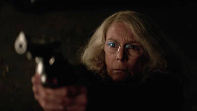 Laurie Strode lies on her back with a gun pointed at Michael Myers in Halloween 2018