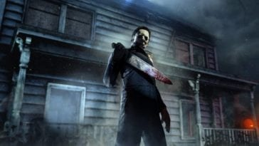 Michael Myers stands outside a dark house holding his bloody knife in front of him as a pumpkin shines in the background