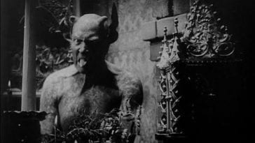 A horned demon in black and white sticks his tongue out while looking into the camera in Haxan