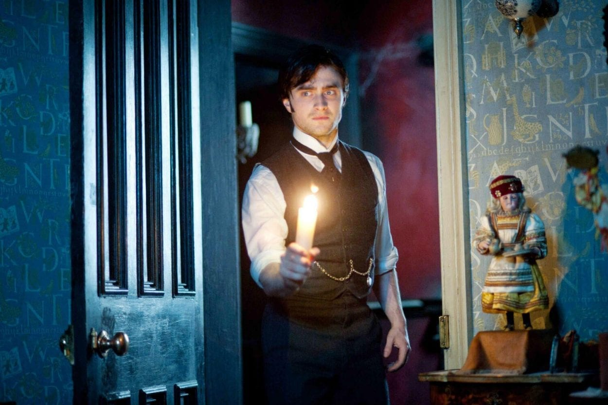 Daniel Radcliffe searches a dark room with a candle