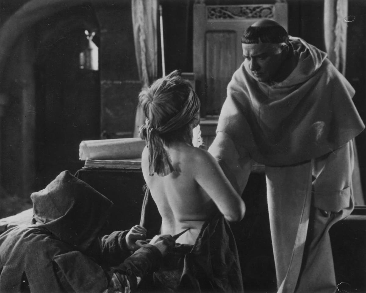 A blindfolded woman is poked in the back with a blade by a hooded figure while a friar stands before her in Haxan.