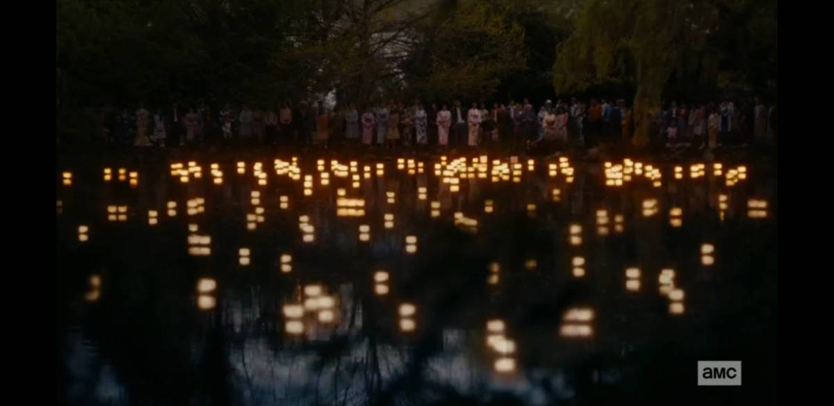 The Japanese citizens watch from the riverbank as lanterns float across the water