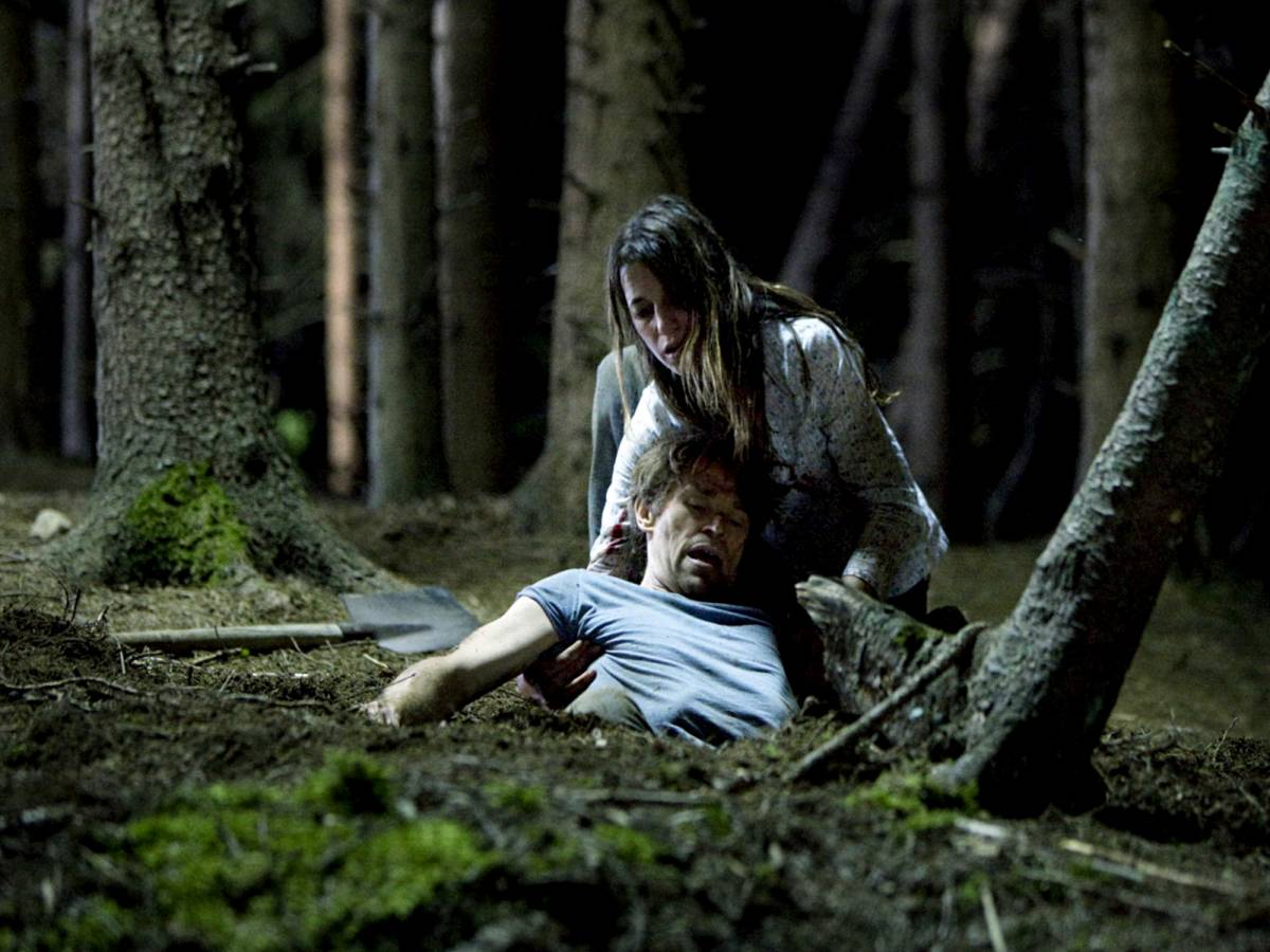 A woman struggles to lift a man out of the ground in Lars von Trier's Antichrist