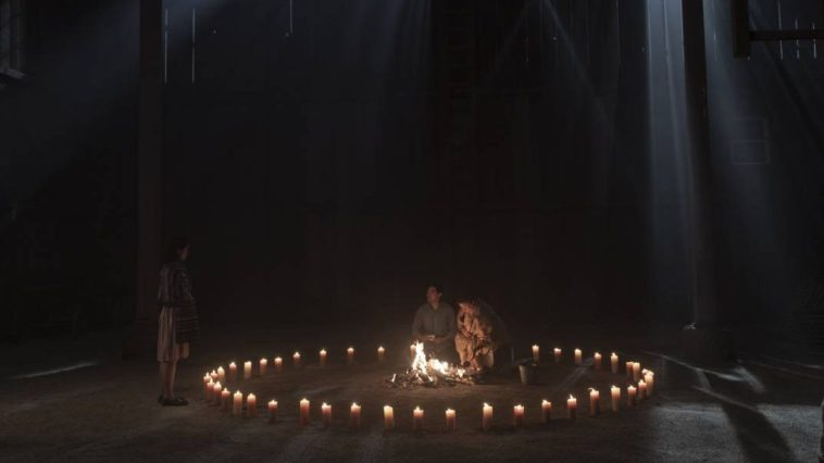 Chester sits in the dark amongst a circle of candles