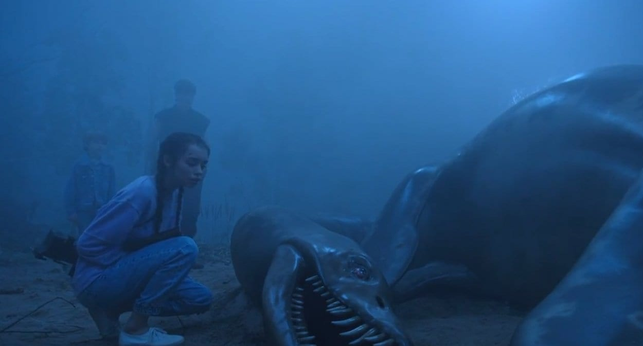 Rose examines the dead lake monster while her brother and friend look on in the background.