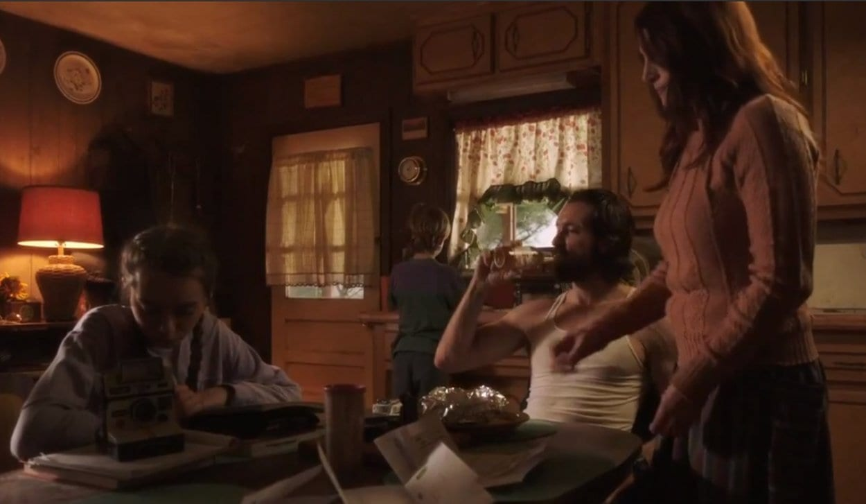 Rose, Chet, Rose's mom and brother sit around the kitchen table while Chet drinks a beer and everyone else appears passive and subdued.