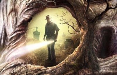 Man holding flashlight peering through a hole