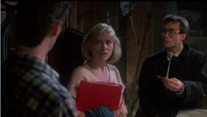Barbara Crampton holds books and looks incredulously at Bruce Abbott in Re-Animator