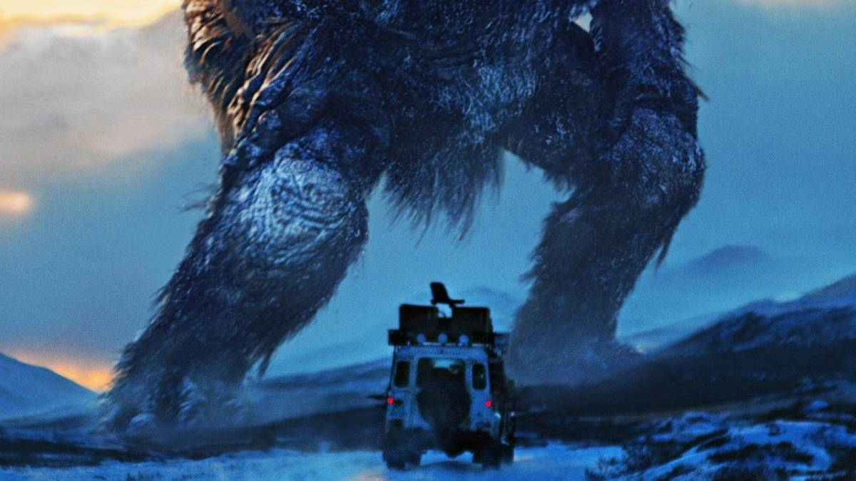 A truck in a snowy mountainscape stops in front of a giant troll who is so large that he is only visible from the hips down in the frame in Trollhunter