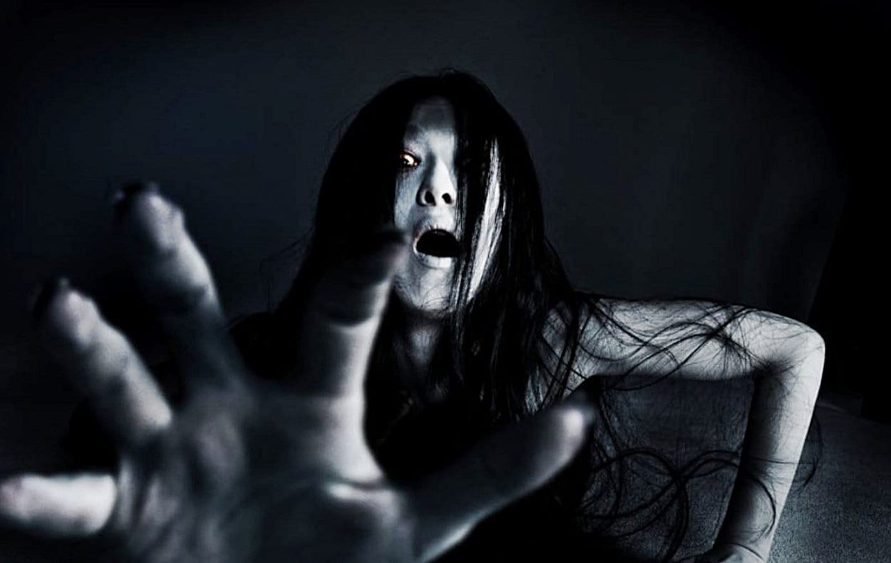 A dark figure of a woman screams and reaches out her hand