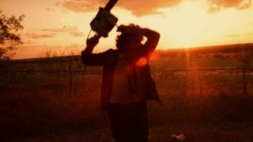 Leatherface sings his chainsaw in frustration on a road while the sun sets
