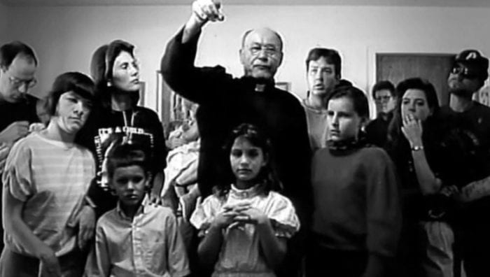 Father Norman Westlin stands around women and children in his home