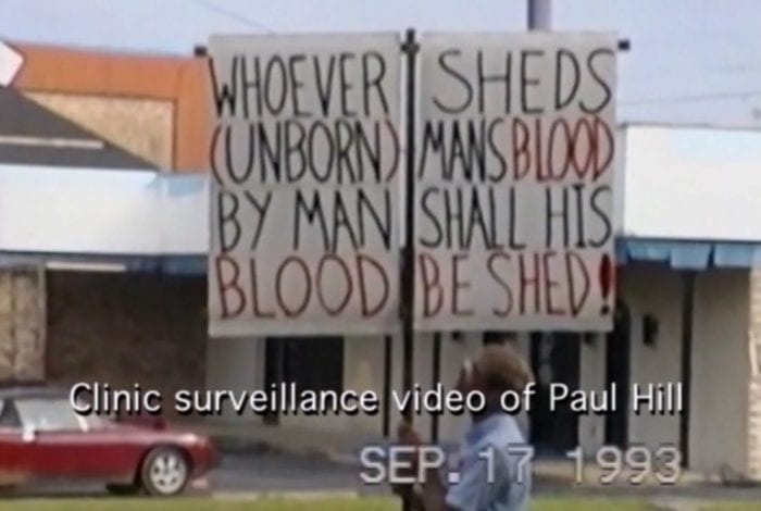Paul Hill holds an anti-abortion sign outside of a clinic in Pensacola, Florida