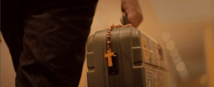 A man walks through a clinic carrying a rosary and a briefcase bomb in Red Christmas