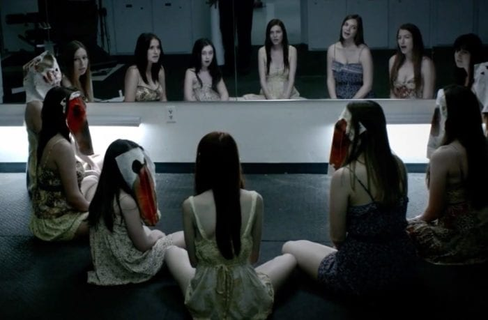 The ghosts of several of the Paymon's family's victims sit in a circle wearing bloody white masks