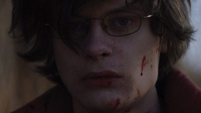 Charlie Tahan's Josh looks off camera with a small amount of blood on his face