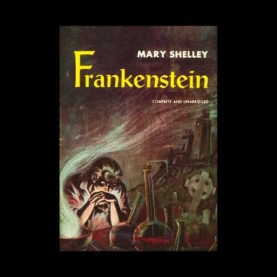Dr. Frankenstein sits at his desk, brooding, with chemistry equipment to his left
