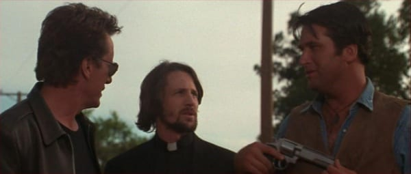 Jack Crow, Father Adam and Montoya are stood side by side, Montoya has a gun drawn and the men plan their next move
