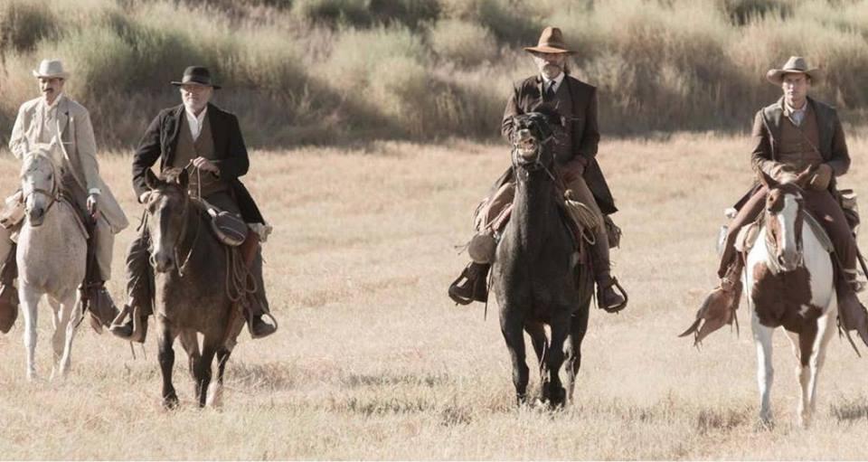 Four men on horseback riding across the plains.
